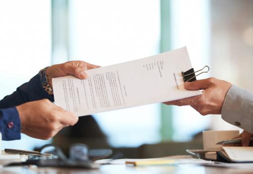 W pomieszczeniu biurowym mężczyzna z prawej strony w szarej koszuli przekazuje mężczyźnie po lewej stronie w granatowej koszuli plik dokumentów przytrzymanych spinaczem klipsowym.